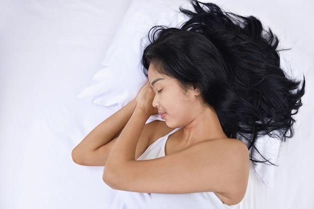 Jovem mulher asiática dormindo com a cabeça deitada por lado