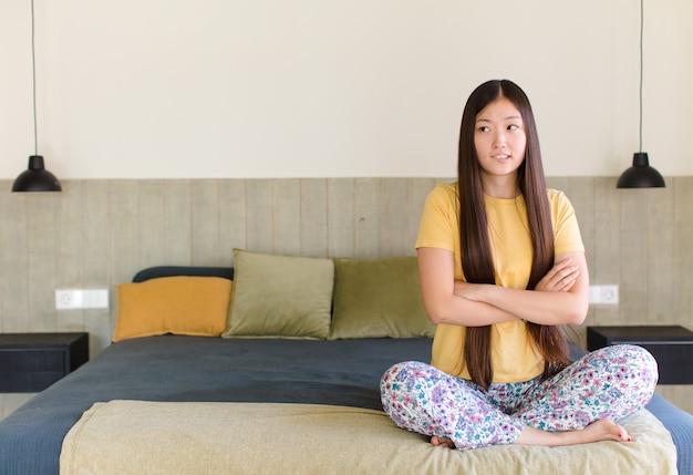 Jovem mulher asiática duvidando ou pensando, mordendo o lábio e sentindo-se insegura e nervosa, procurando copiar o espaço ao lado