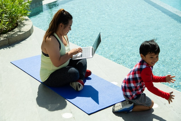 Jovem mulher asiática e filho menino sorrindo enquanto estava deitado na esteira de treinamento online de ioga. estilo de vida saudável e conceitos de esporte.