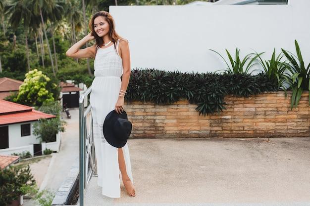 Jovem mulher asiática elegante com vestido boho branco, estilo vintage, natural, sorridente, feliz, férias tropicais, hotel, fundo de palmeiras