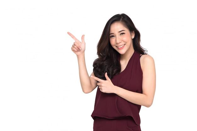 Jovem mulher asiática elegante sorrindo e apontando para o espaço vazio cópia isolado