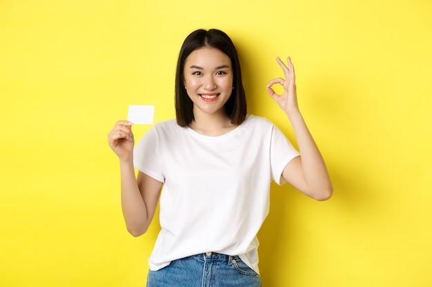 Jovem mulher asiática em casual t-shirt branca, mostrando o cartão de crédito de plástico e o gesto certo, recomendo o banco, sorrindo para a câmera, fundo amarelo.