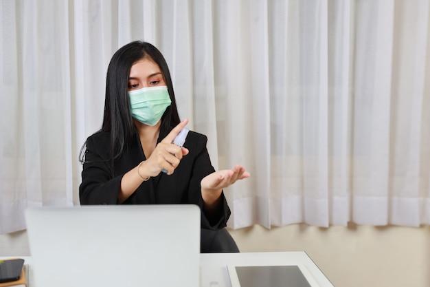 Jovem mulher asiática em terno waring proteger a máscara e usar álcool spray desinfetante de mãos para cuidados de saúde e sentado no escritório, trabalhando no computador e smartphone. novo conceito de distanciamento normal e social