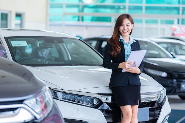 Jovem mulher asiática em um conceito do assistente de serviço do aluguer de carros / vendas carro na sala de exposições