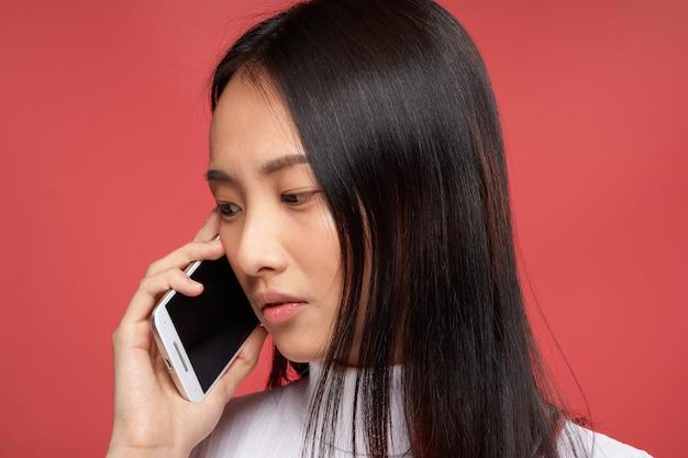 Jovem mulher asiática em um espaço azul posando, emoções diferentes, mock up