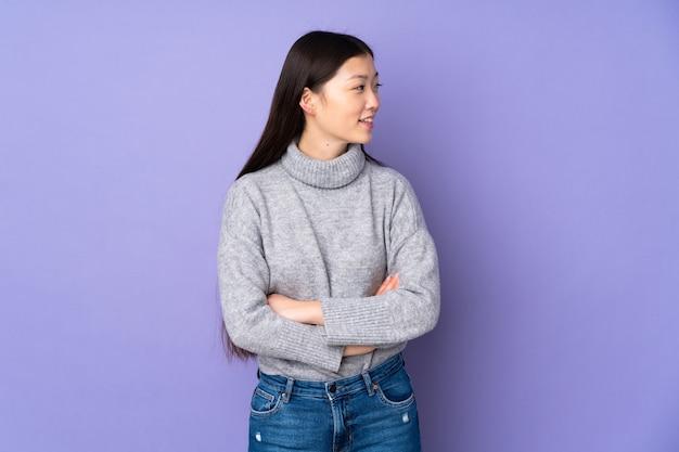 Jovem mulher asiática em um fundo isolado, olhando para o lado e sorrindo