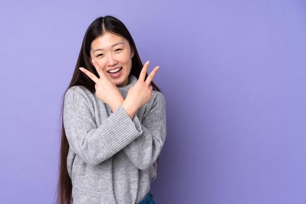 Jovem mulher asiática em um fundo isolado sorrindo e mostrando sinal de vitória