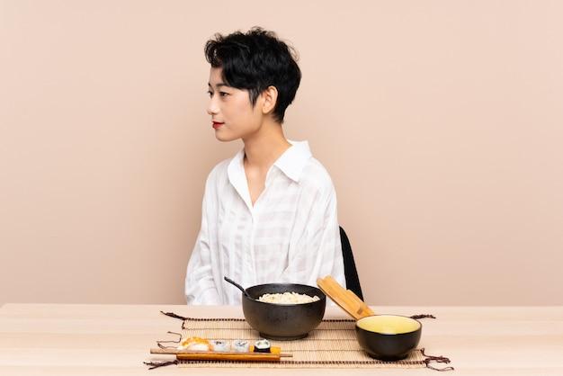 Jovem mulher asiática em uma mesa com tigela de macarrão e sushi, olhando de lado