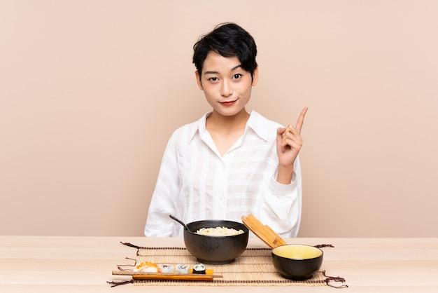 Jovem mulher asiática em uma mesa com uma tigela de macarrão e sushi apontando com o dedo indicador uma ótima idéia