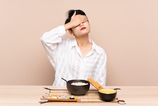 Jovem mulher asiática em uma mesa com uma tigela de macarrão e sushi cobrindo os olhos pelas mãos