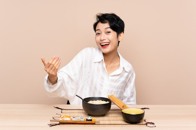 Jovem mulher asiática em uma mesa com uma tigela de macarrão e sushi, convidando para vir