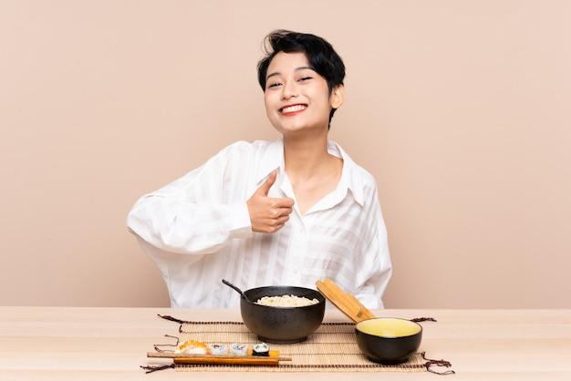 Jovem mulher asiática em uma mesa com uma tigela de macarrão e sushi, dando um polegar para cima gesto