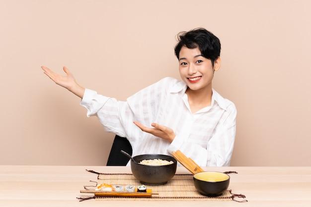 Jovem mulher asiática em uma mesa com uma tigela de macarrão e sushi, estendendo as mãos para o lado para convidar para vir