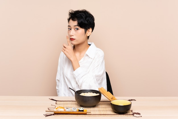 Jovem mulher asiática em uma mesa com uma tigela de macarrão e sushi, fazendo o gesto de silêncio