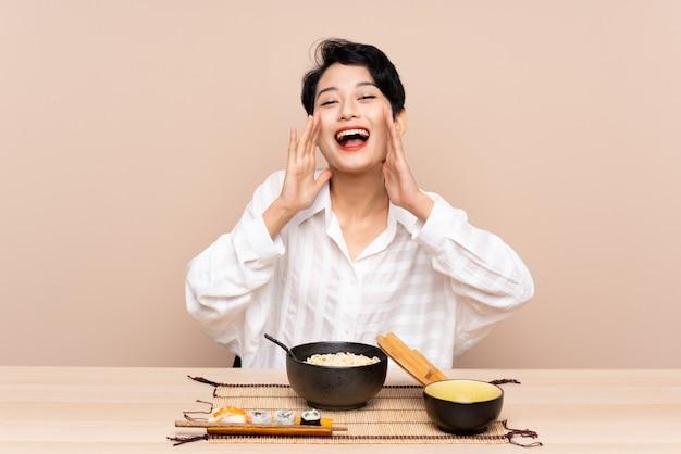 Jovem mulher asiática em uma mesa com uma tigela de macarrão e sushi gritando com a boca aberta