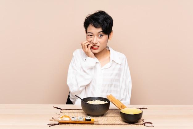 Jovem mulher asiática em uma mesa com uma tigela de macarrão e sushi nervoso e assustado