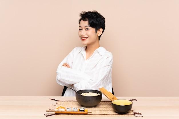 Jovem mulher asiática em uma mesa com uma tigela de macarrão e sushi, olhando para o lado