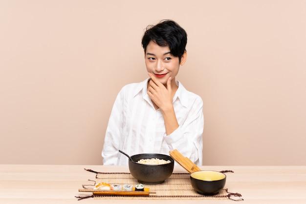 Jovem mulher asiática em uma mesa com uma tigela de macarrão e sushi, pensando uma idéia