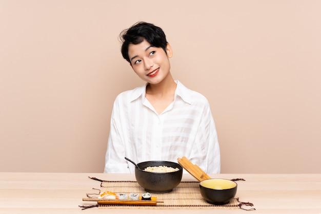 Jovem mulher asiática em uma mesa com uma tigela de macarrão e sushi rindo e olhando para cima