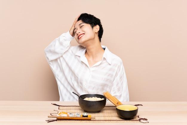 Jovem mulher asiática em uma mesa com uma tigela de macarrão e sushi rindo