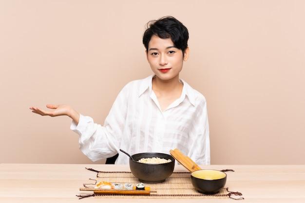 Jovem mulher asiática em uma mesa com uma tigela de macarrão e sushi segurando copyspace imaginário na palma da mão