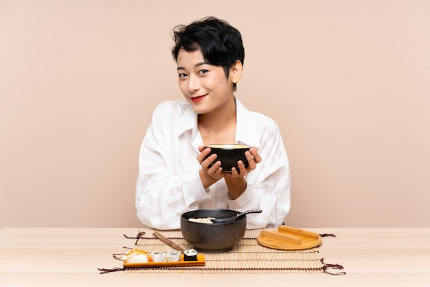 Jovem mulher asiática em uma mesa com uma tigela de macarrão e sushi