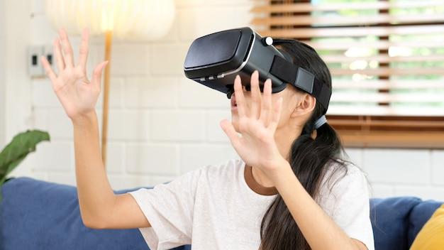 Jovem mulher asiática emocionante no fone de ouvido vr, olhando para cima e tentando tocar objetos na realidade virtual em casa, sala de estar, menina adolescente jogando fone de ouvido vr, pessoas e tecnologia de realidade virtual de lazer