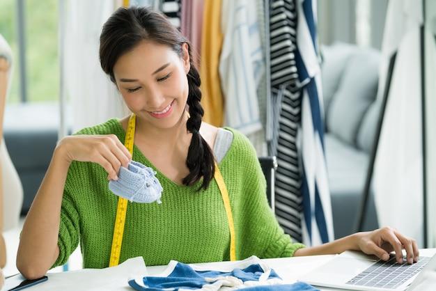Jovem mulher asiática empresário / designer de moda para roupas de bebê, trabalhando em estúdio