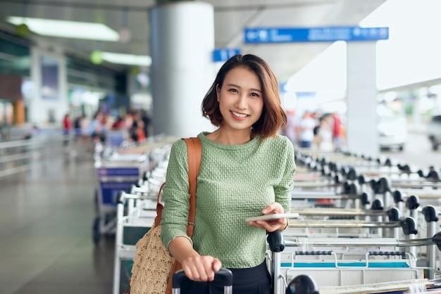 Jovem mulher asiática esperando na calçada por sua carona, que ela reservou por meio de um aplicativo de chamada de carona.