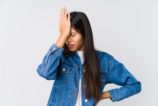 Jovem mulher asiática esquecendo algo, batendo na testa com a palma da mão e fechando os olhos.