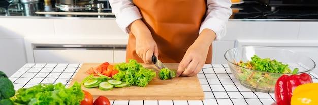 Jovem mulher asiática está preparando uma salada de vegetais com alimentação saudável