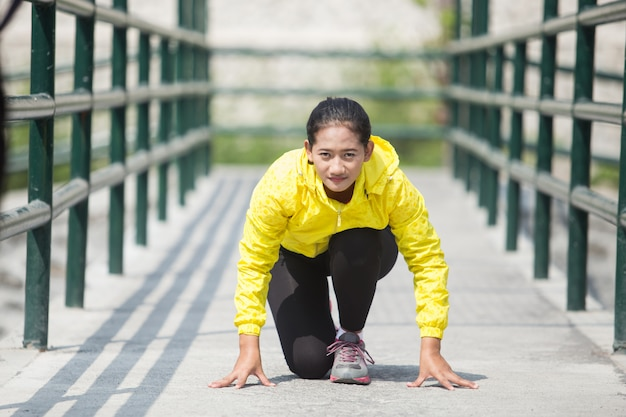 Jovem mulher asiática exercitando ao ar livre no casaco de néon amarelo, gett