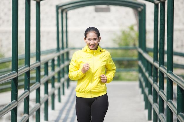 Jovem mulher asiática exercitando ao ar livre no casaco de néon amarelo, jogg