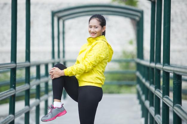 Jovem mulher asiática exercitando ao ar livre no casaco de néon amarelo, stre