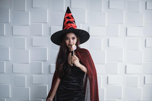 Jovem mulher asiática fantasiada de bruxa e segurar o pirulito na parede branca do conceito de halloween. retrato de mulher adolescente vestida de bruxa para celebrar o festival de halloween.