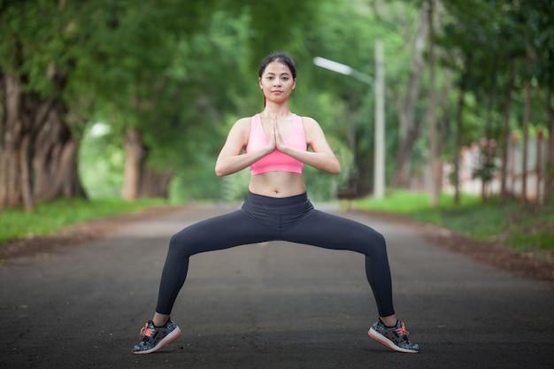 Jovem mulher asiática fazendo alguns exercícios de aquecimento antes de correr no parque na manhã
