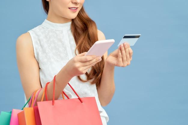 Jovem mulher asiática fazendo compras online com smartphone e pagando com cartão de crédito em fundo azul do estúdio
