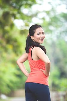 Jovem mulher asiática fazendo exercício ao ar livre em um parque, esticando