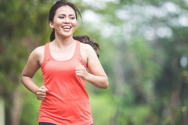 Jovem mulher asiática fazendo exercício ao ar livre em um parque, movimentando-se