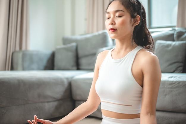 Jovem mulher asiática fazendo exercícios de ioga na academia em casa, estilo de vida feminino saudável com treinamento esportivo fitness em casa, garota fazendo exercícios físicos ativos no corpo, quarto interno da casa, relaxamento e bem-estar