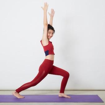 Jovem mulher asiática fazendo exercícios sobre um fundo claro