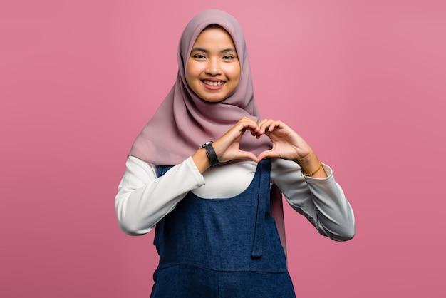 Jovem mulher asiática fazendo sinal de amor com as mãos