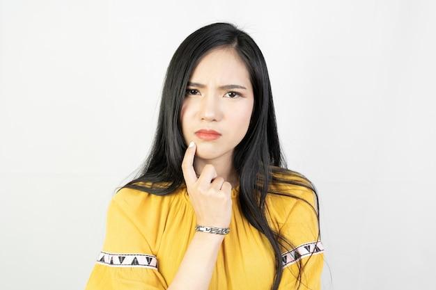 Jovem mulher asiática fazendo uma pose de pensamento em branco.