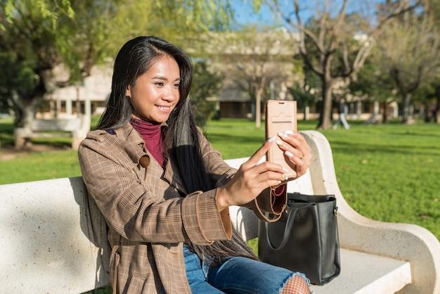 Jovem mulher asiática fazendo uma videochamada sentada em um banco do parque