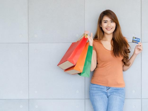 Jovem mulher asiática feliz bonita em pé está usando cartão de crédito ou débito e carregando sacolas de compras