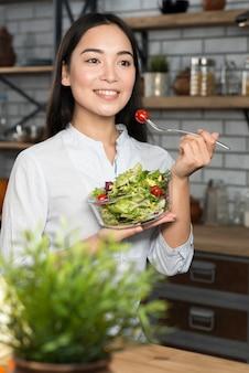 Jovem mulher asiática feliz comendo salada verde saudável