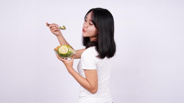Jovem mulher asiática feliz comendo uma salada saudável com uma superfície branca isolada
