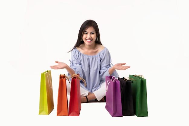 Jovem mulher asiática feliz que leva sacos de compras isolados