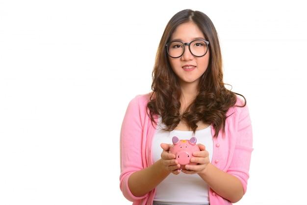 Jovem mulher asiática feliz segurando o cofrinho isolado contra o branco