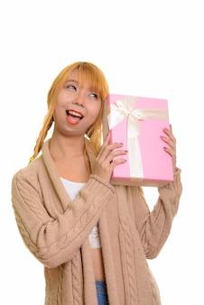 Jovem mulher asiática feliz sorrindo e adivinhando uma caixa de presente